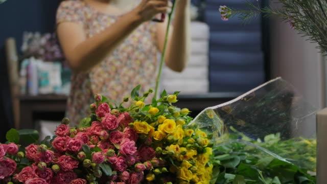 vídeos de stock, filmes e b-roll de um florista está preparando buquê de flores - bouquet