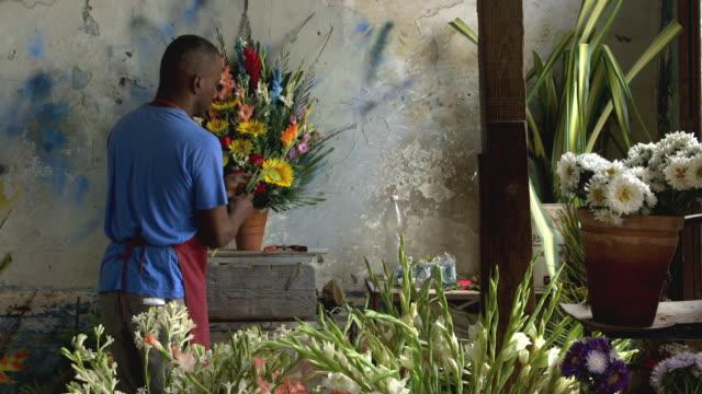 ms a florist prepares a bouquet in his shop / havana, cuba - フローリスト点の映像素材/bロール