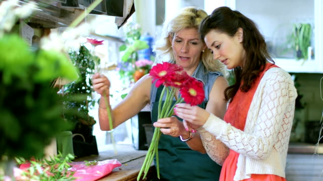 MS Florist shows a Apprentice how to gather flowers into a bouquet