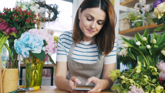 florist using her smart phone. - small business stock videos & royalty-free footage