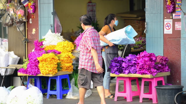 florist walking out from an orchid shop carrying a bundle of flowers to be delivered - orchid stock videos & royalty-free footage