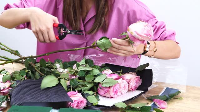 vídeos de stock e filmes b-roll de florist woman makes a flower arrangement at flower shop, small business - ramo parte de uma planta