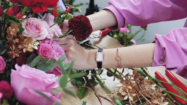 花屋の女性は、花屋、中小企業で花の配置を作ります - フローリスト点の映像素材/bロール