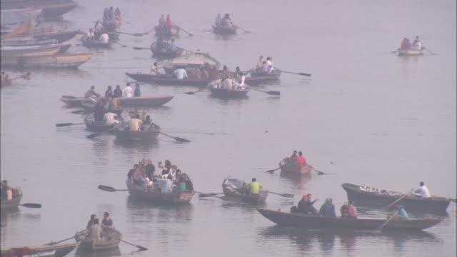 a flotilla of rowboats crowds a river in india. - flotilla stock videos & royalty-free footage