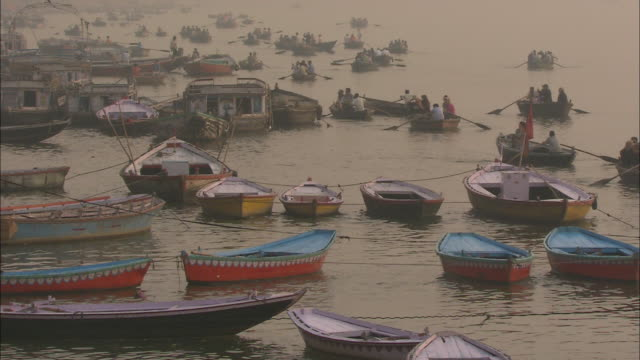 a flotilla of rowboats moor on the ganges river in india. - flotilla stock videos & royalty-free footage
