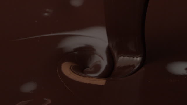 vídeos de stock e filmes b-roll de flow of brown chocolate pouring down in slow motion tabletop - moldura completa