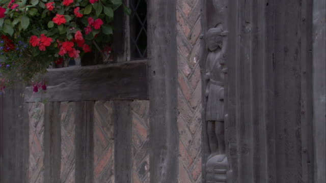 a flower basket moves in the wind outside a medieval house in lavenham, suffolk, england. - lavenham stock-videos und b-roll-filmmaterial