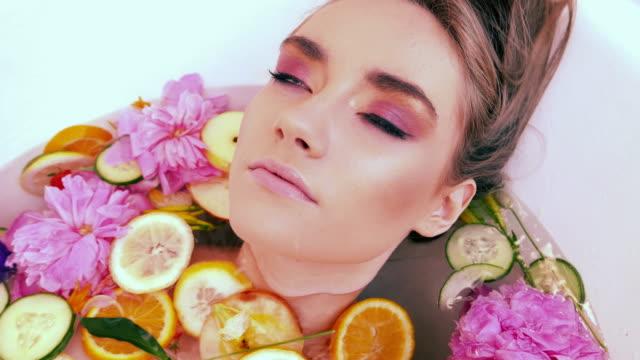 vidéos et rushes de bain de fleurs. une expression satisfaite sur le visage de la jeune fille. en prenant soin de vous-même et de votre santé. - bouche humaine