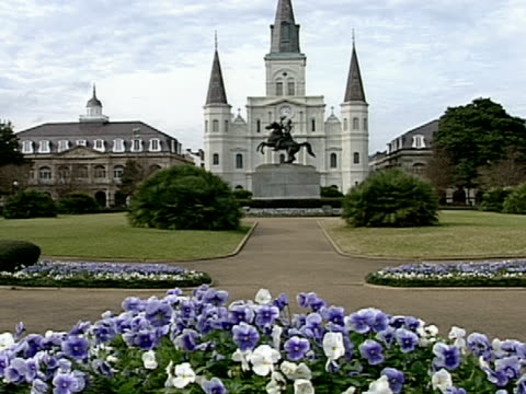 vídeos de stock e filmes b-roll de flower beds and a statue highlight the landscape at st. philip's cathedral in new orleans, louisiana. - cathedral