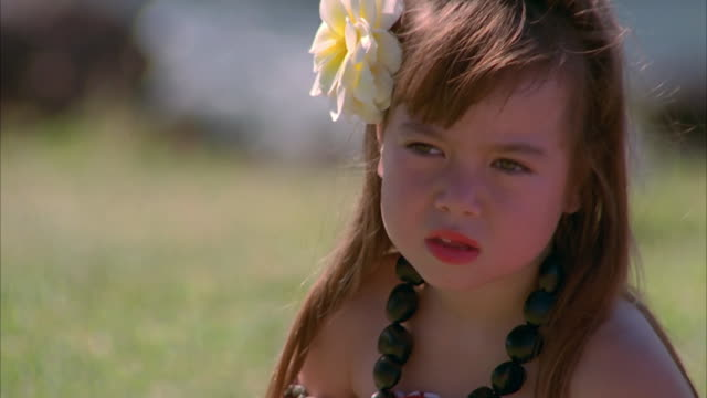 A flower clings to a little girls hair in Maui. Available in HD.