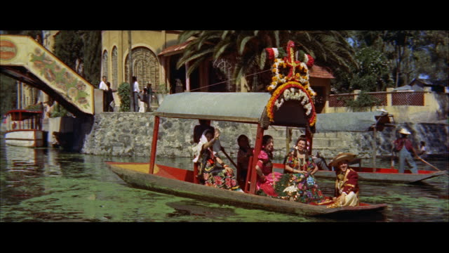 ms pan flower covered boats on canals of xochimilco garden / mexico - anno 1957 video stock e b–roll