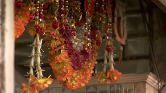 Flower garlands hang from a shop ceiling.