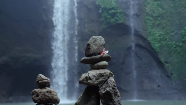 flower on stack of rocks by waterfall - balance stock videos and b-roll footage