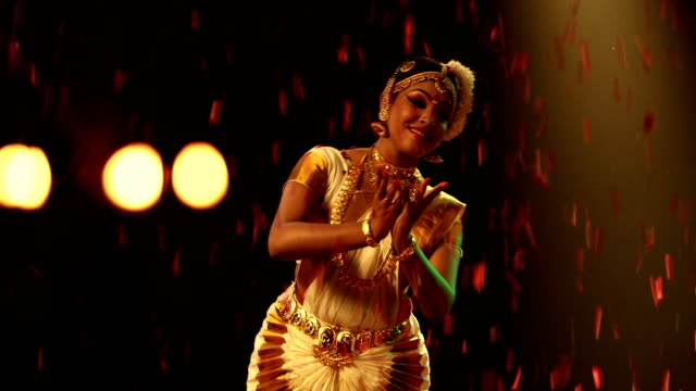 ms flower petals falling while woman performing mohiniyattam dance on stage / india - indian ethnicity stock videos and b-roll footage