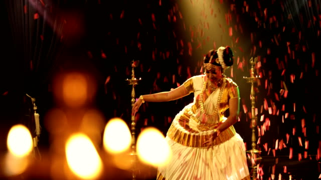 ms flower petals falling while woman performing mohiniyattam dance on stage / india - performing arts event stock videos & royalty-free footage