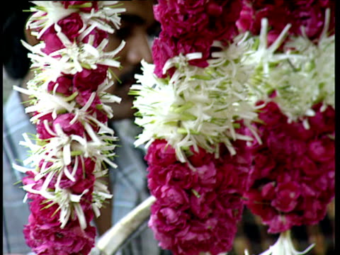 Flower seller trims garlands of flowers dangling from his stall in flower market Ahmedabad