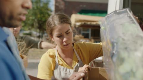 vidéos et rushes de flower shop owners and delivery driver discuss flower bouquets next to delivery truck - décharger
