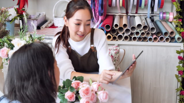 flower shopkeeper asian woman received orders to prepare for in-store sales, a japanese woman with professional florists, small business concept. - fioraio negozio video stock e b–roll