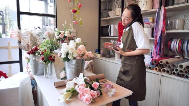 フラワーショップキーパーのアジア人女性は、店内販売の準備を命じ、プロの花屋を持つ日本人女性、中小企業のコンセプトを受けました。 - フローリスト点の映像素材/bロール