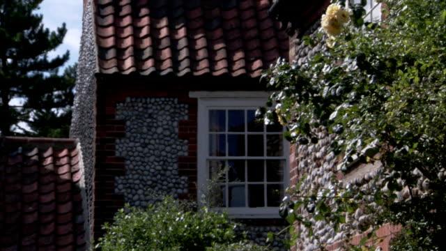 vídeos y material grabado en eventos de stock de flowering shrubs bloom around a flint and brick home. available in hd. - casa de ladrillo