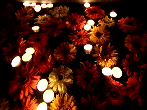 Flowers and candles floating on water at night India