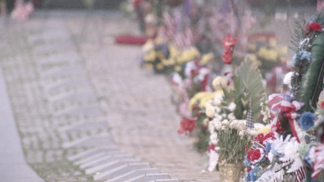 flowers and flags line the vietnam veterans memorial. - vietnam veterans memorial video stock e b–roll