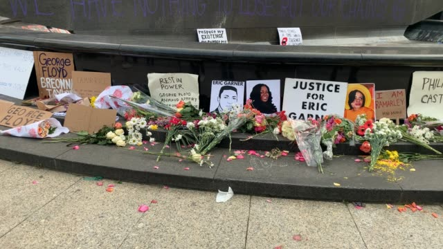 "flowers and signs with text of ""george floyd"" and ""eric garner"" are left after as demonstrators gather to protest the recent death of george floyd,... - ひざまずく点の映像素材/bロール"