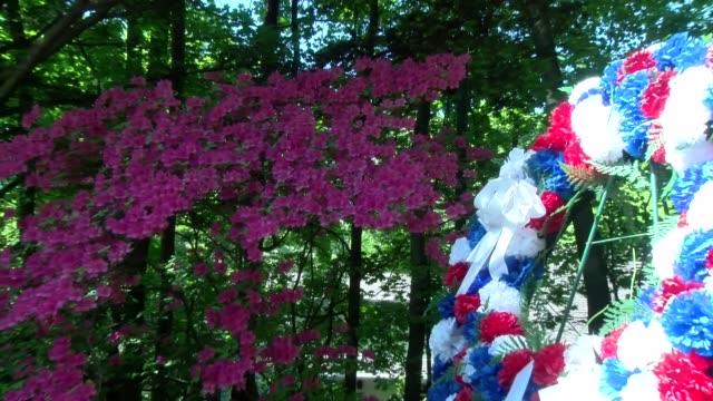 vidéos et rushes de flowers and wreath at town memorial day park - salmini
