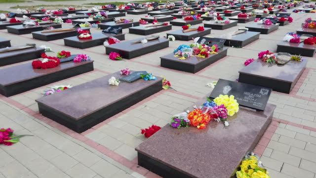 flowers are seen on the memorial stones of the 372 victims of one of the largest massacres of the war on may 1, 2019 in meje, kosovo. a recent... - serbia stock videos & royalty-free footage