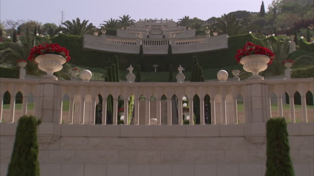 flowers fill stone urns in the hanging gardens of haifa in israel. available in hd - haifa video stock e b–roll