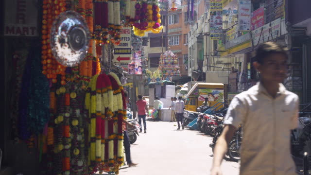 flowers garland market stall at bangalore next to a hindu temple - tradition stock-videos und b-roll-filmmaterial