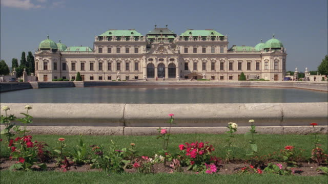 Flowers grow before the reflecting pool at Belvedere Palace in Vienna.