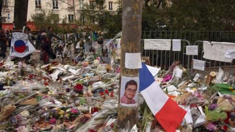 vidéos et rushes de flowers, messages, candles and portraits paying tributes to victims of terrorism near le bataclan concert hall in paris, france. - respect