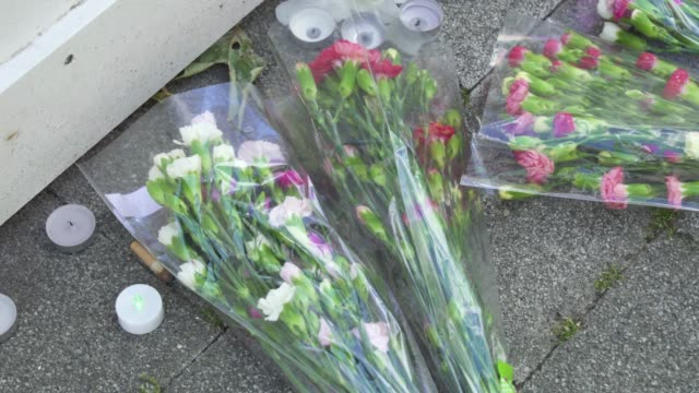flowers next to a wall where messages of support have been written surrounding grenfell tower in west london on june 14 on the third anniversary of... - fire natural phenomenon stock videos & royalty-free footage