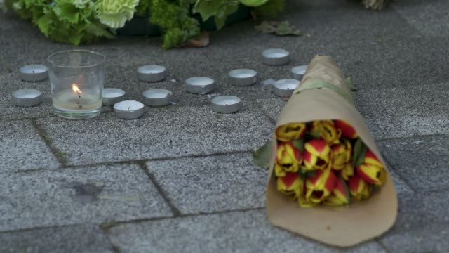 flowers next to a wall where messages of support have been written, surrounding grenfell tower in west london on june 14 on the third anniversary of... - surrounding wall点の映像素材/bロール