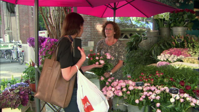 stockvideo's en b-roll-footage met cu flowers zoom out of woman selling flowers to another woman - business or economy or employment and labor or financial market or finance or agriculture