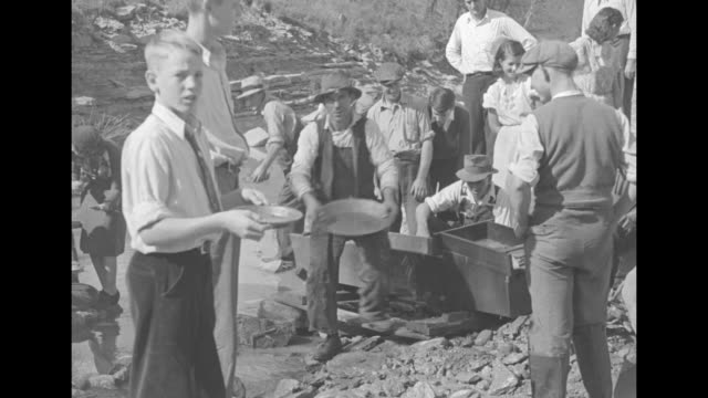 flowing river / men standing next to entrance to mine shaft in side of hill / shot from above of sluice going down hill / people panning for gold /... - panning stock videos & royalty-free footage
