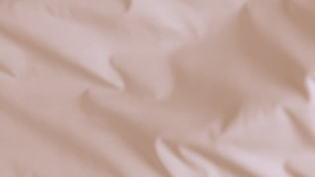 Flowing silky beige jersey fabric background, closeup