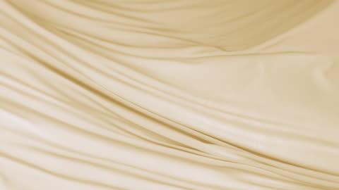 vidéos et rushes de flowing silky gold jersey fabric background, closeup - en l'air