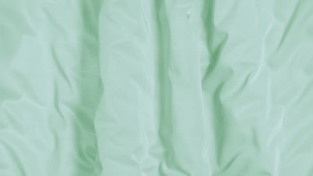 flowing silky jersey green fabric background, closeup - pastello video stock e b–roll