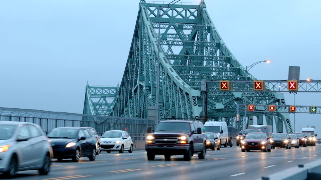 flowing traffic on montreal jacques-cartier bridge at dawn zoom out version hd - montreal video stock e b–roll