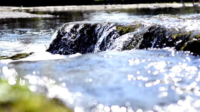 stockvideo's en b-roll-footage met flowing water and bokeh of a canal - softfocus
