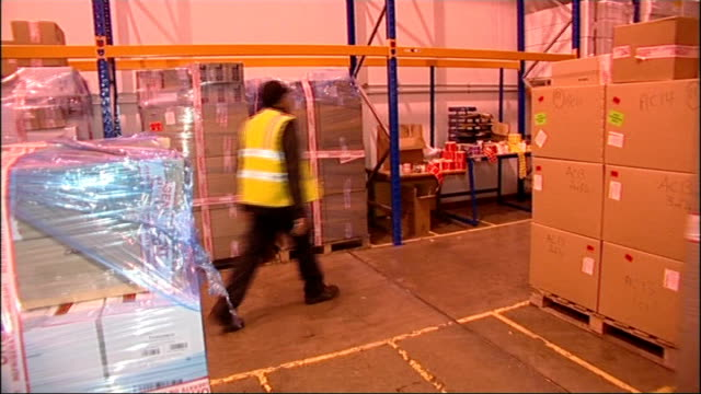 stockvideo's en b-roll-footage met leftover swine flu vaccine to be used as death toll reaches 50; england: ext various of worker moving boxes of flu vaccine in warehouse - varkensgriep