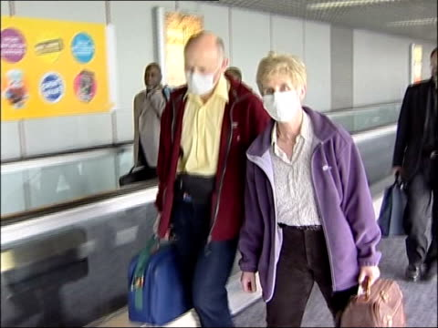 int passengers returning from beijing along in face masks fans at football match int patient receiving vaccination ext chiron vaccines sign outside... - epidemie stock-videos und b-roll-filmmaterial