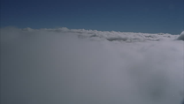 fluffy clouds and a blue sky with a mountain landscape below. - 天国点の映像素材/bロール