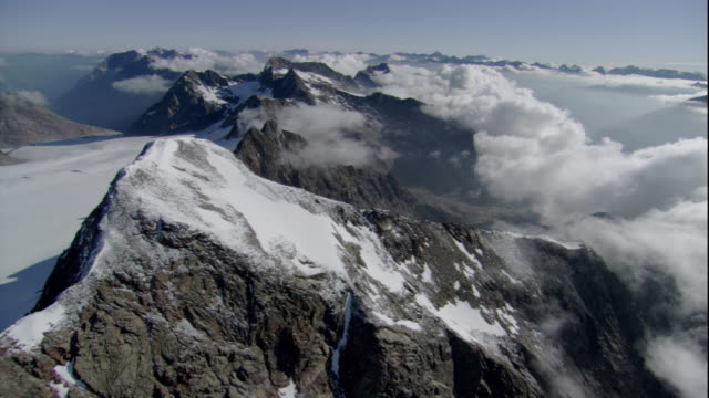 Fluffy clouds encircle glaciers at the base of the Austrian Alps. Available in HD.