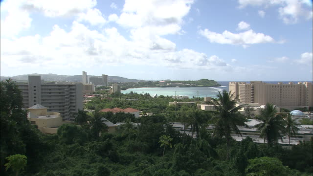 fluffy clouds float above palm trees and buildings in guam. - guam stock videos and b-roll footage