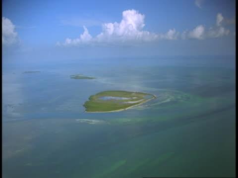 vidéos et rushes de fluffy clouds float above small islands in the bahamas. - angle de prise de vue