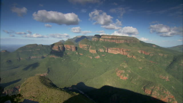 fluffy clouds float above the blyde river canyon in south africa. available in hd - blyde river canyon stock videos and b-roll footage