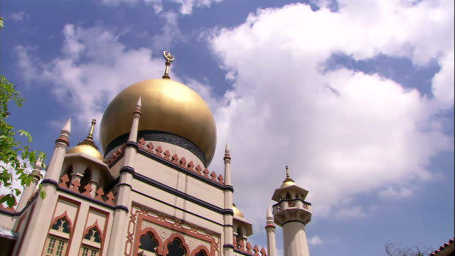 fluffy clouds float above the golden dome of the sultan mosque in singapore. - sultan mosque singapore stock videos and b-roll footage